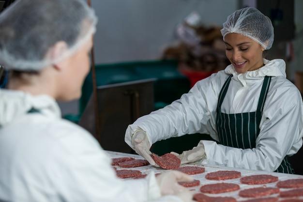 Mujeres carniceros procesando hamburguesa