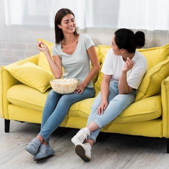 Mujeres en casa en el sofá charlando y comiendo palomitas de maíz