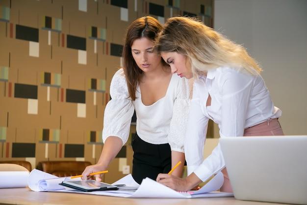Mujeres caucásicas creando un nuevo diseño y escribiendo en papel