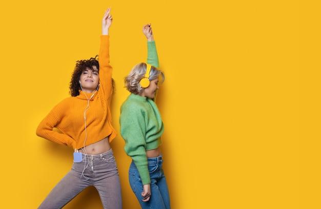 Mujeres caucásicas con pelo rizado escuchando música y bailando con auriculares en una pared amarilla con espacio libre