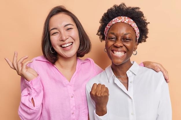 Las mujeres celebran los logros se sienten muy positivas sonríen ampliamente de pie cerca unas de otras vestidas con camisas en beige