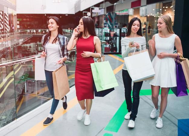Mujeres en el centro comercial hablando por teléfono