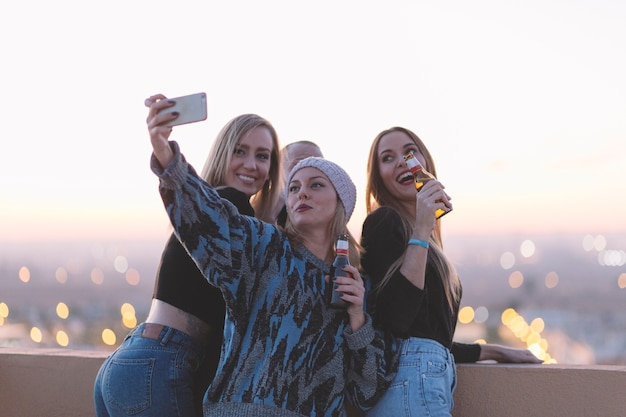 Mujeres con cerveza tomando selfie en techo