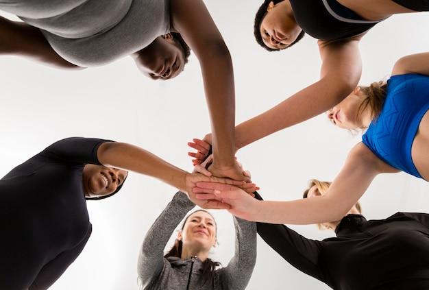 Mujeres en clase de gimnasia dándose la mano