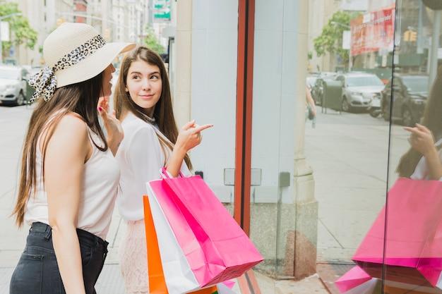 Mujeres con coloridos bolsos de compras cerca de la ventana de la tienda
