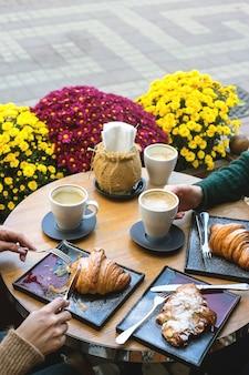 Las mujeres comen cruasanes en una cafetería con capuchino. mesa de cerca.