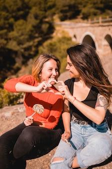 Mujeres con piruletas mostrando gesto de corazón
