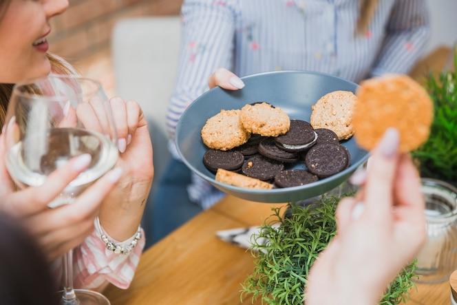 Mujeres con vino comiendo galletas