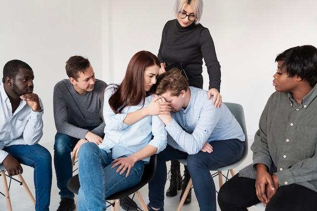 Mujeres consolando paciente masculino de rehabilitación