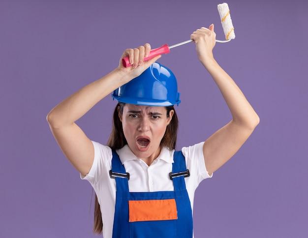 Mujeres constructoras jóvenes enojadas en uniforme levantando mini rodillo de pintura aislado en la pared púrpura