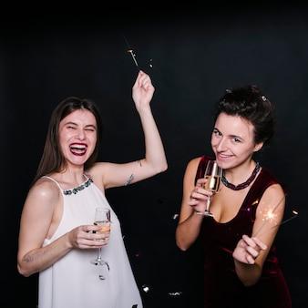 Mujeres con copas de champagne y bengalas.