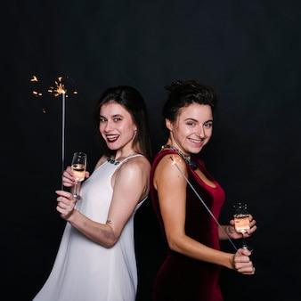 Mujeres con copas de champán y bengalas.