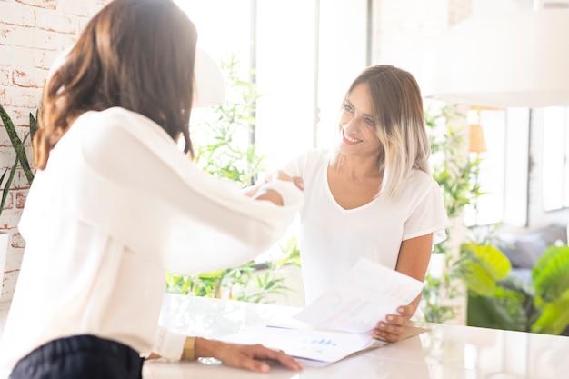 Mujeres corporativas profesionales dándose la mano