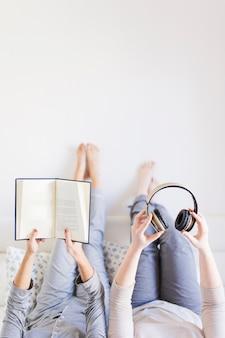 Mujeres de cultivos con libros y auriculares