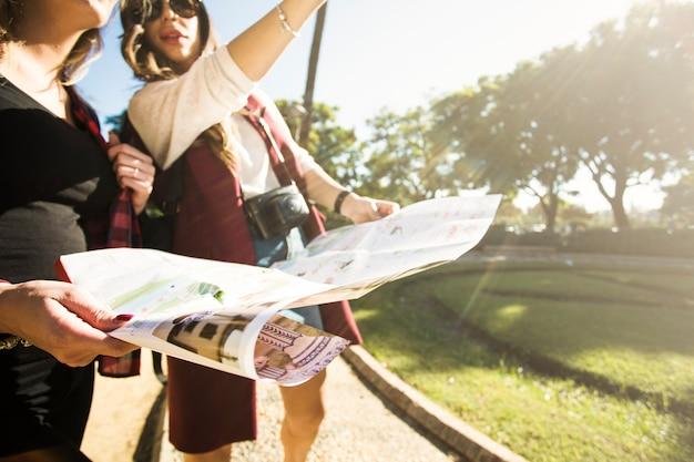 Mujeres de cultivos con el mapa de pie en la calle
