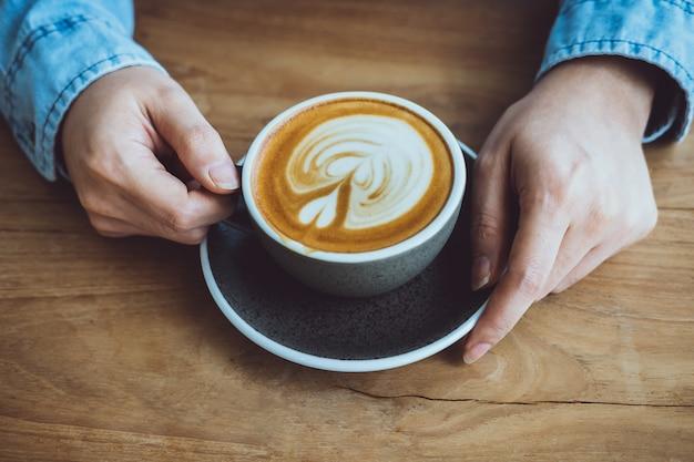 Las mujeres dan sostener la taza de café en la tabla marrón.
