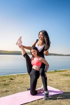 Mujeres delgadas jóvenes haciendo ejercicio de estiramiento relajante y calentamiento después de trotar y correr en el parque cerca del lago