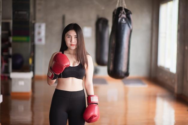 Mujeres del deporte que entrenan al boxeo en el gimnasio