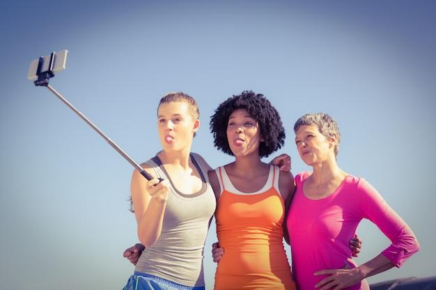 Mujeres deportistas posando y tomando selfies con selfiestick.