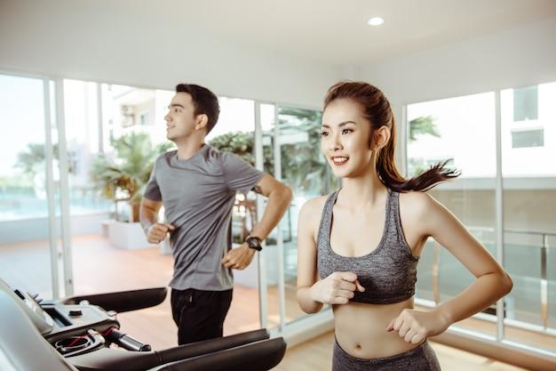 Las mujeres deportivas asiáticas jovenes corren en la máquina en el centro del gimnasio