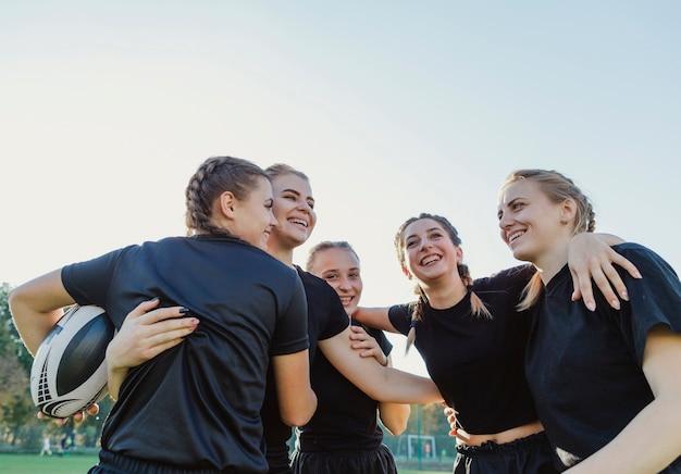 Mujeres deportivas sonrientes que se abrazan