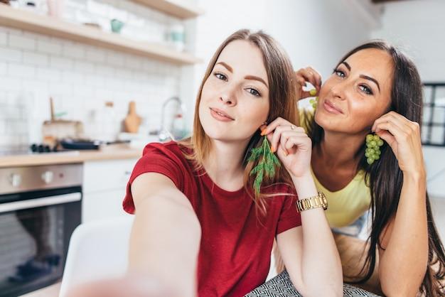 Mujeres desayunando en la cocina jugando con la comida y tomando selfie.