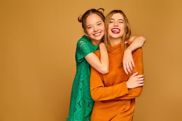 Mujeres despreocupadas aisladas en la pared de oro modelos positivos volviéndose locos