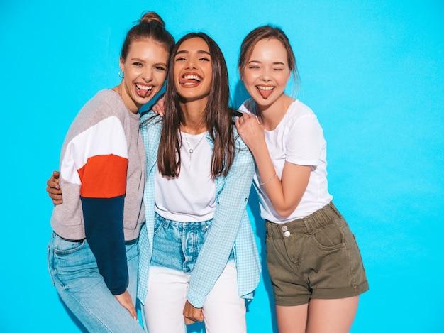 Mujeres despreocupadas atractivas que presentan cerca de la pared azul en estudio. modelos positivos divirtiéndose y abrazándose. muestran lengua