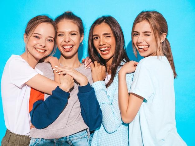 Mujeres despreocupadas atractivas que presentan cerca de la pared azul en estudio. modelos positivos divirtiéndose y abrazándose. muestran lenguas