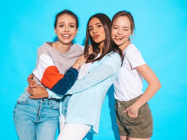 Mujeres despreocupadas atractivas que presentan cerca de la pared azul en estudio. modelos positivos divirtiéndose y abrazándose