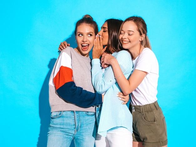 Mujeres despreocupadas atractivas que presentan cerca de la pared azul en estudio. modelos positivos que se vuelven locos y se divierten. compartan secretos, chismes