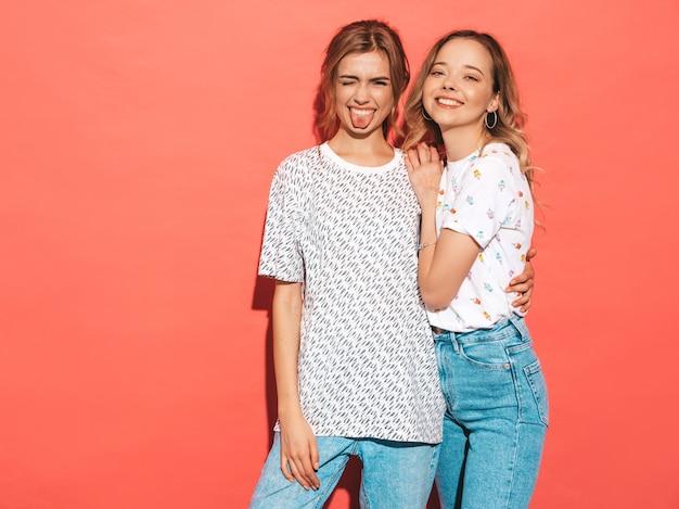 Mujeres despreocupadas atractivas que presentan la pared azul rosada. modelos positivos divirtiéndose y mostrando lengua