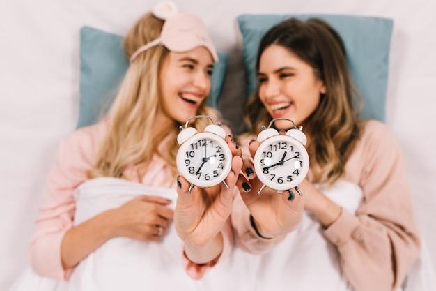 Mujeres despreocupadas en la cama por la noche