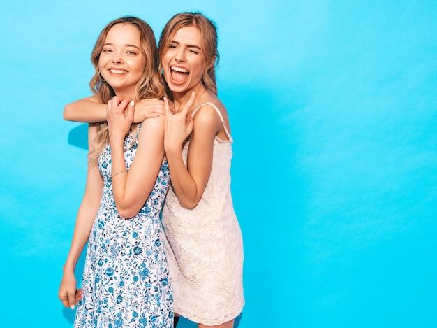 Mujeres despreocupadas sexy posando junto a la pared azul. divirtiéndose y abrazándose. los modelos muestran una buena relación. la hembra hace cara de pato