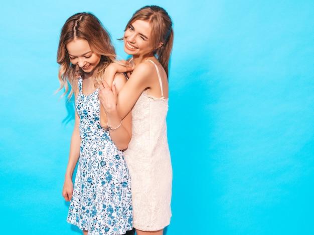Mujeres despreocupadas sexy posando junto a la pared azul. divirtiéndose y abrazándose