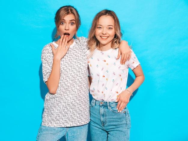 Mujeres despreocupadas sexy posando junto a la pared azul. modelos positivos divirtiéndose emociones faciales sorprendidas