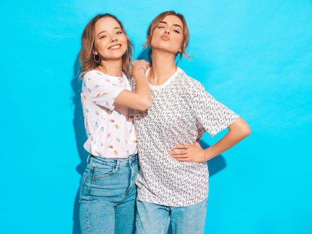 Mujeres despreocupadas sexy posando junto a la pared azul. modelos positivos divirtiéndose. guiña y hace cara de pato