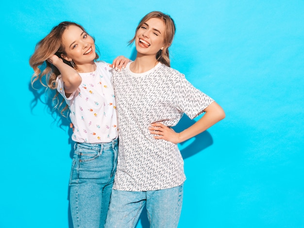 Mujeres despreocupadas sexy posando junto a la pared azul. modelos positivos divirtiéndose. guiña y muestra la lengua