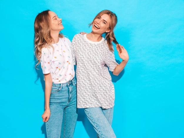 Mujeres despreocupadas sexy posando junto a la pared azul. modelos positivos divirtiéndose