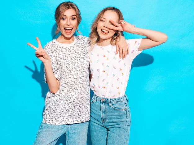 Mujeres despreocupadas sexy posando junto a la pared azul. modelos positivos que se divierten. muestran signo de la paz y lengua