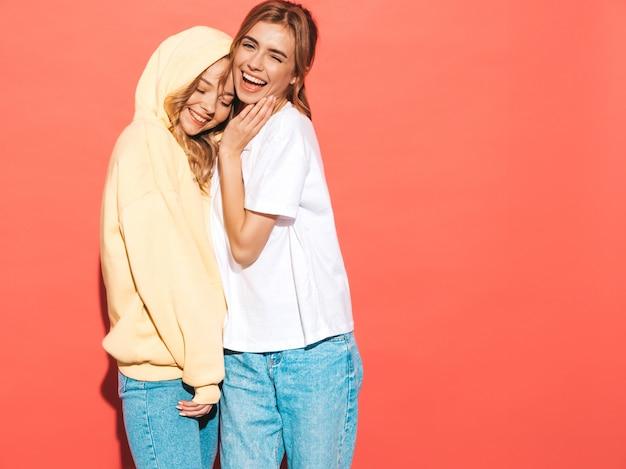 Mujeres despreocupadas sexy posando junto a la pared de color rosa. modelos positivos divirtiéndose