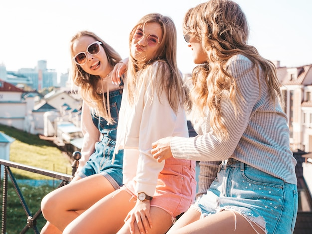 Mujeres despreocupadas y sexy sentadas en la barandilla de la calle y comunicándose. modelos positivos divirtiéndose