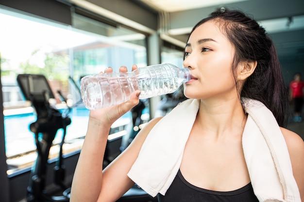 Las mujeres después del ejercicio beben agua de botellas y pañuelos en el gimnasio.