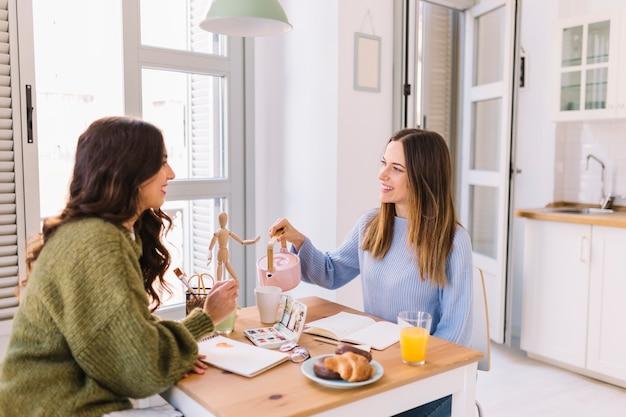 Mujeres dibujando y vertiendo té