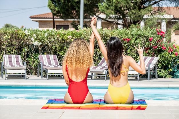 Mujeres de diferentes etnias en trajes de baño con las manos sobre una bandera del orgullo gay.