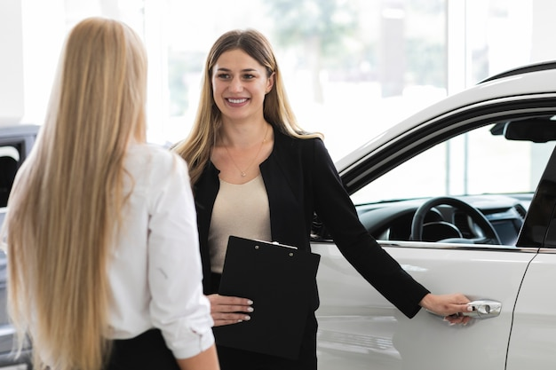 Mujeres discutiendo en la sala de exposición de automóviles