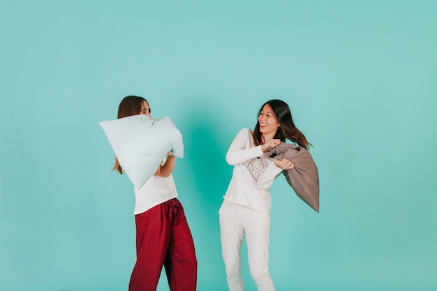 Mujeres divertidas que tienen pelea de almohadas