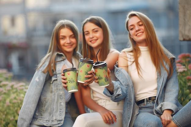 Mujeres divirtiéndose en la calle tomando un café