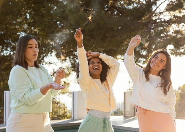Mujeres divirtiéndose con fuegos artificiales.