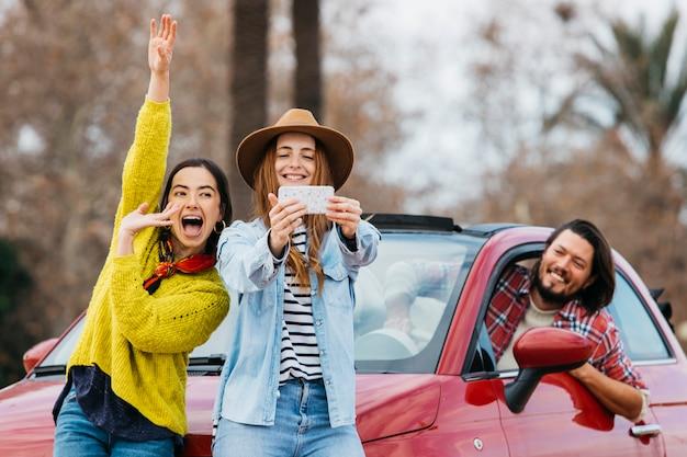 Mujeres divirtiéndose y tomando autofotos en un teléfono inteligente cerca del hombre que se inclina hacia fuera del auto